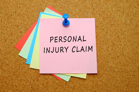 personal injury claim written on colored sticker notes over cork board background Foto de archivo