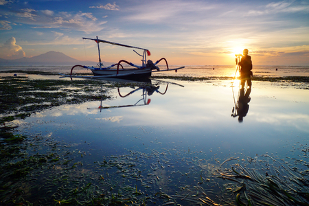 photographer taking Sunrise photo, traditional fishing boats with silhouette at Sanur Beach Bali Indonesia