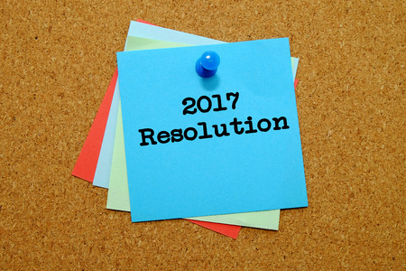 CHALLENGING: 2017 Resolution written on colored sticker notes over cork board background.