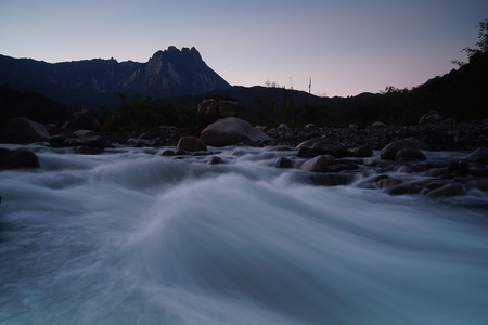 lows: Beautiful Shallow Rapid River With Mount Kinabalu In Background