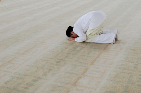 muslim man praying, man prostrating during prayers
