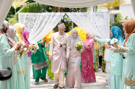 Kuala Lumpur, Malaysia  March 22, 2014. Just married Malay couple walking and holding hands is being congratulating by their guests.