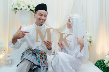 solemnization: Kuala Lumpur, Malaysia  April 5, 2014. Just married Malay couple showing props and cheerful their solemnization event. Editorial