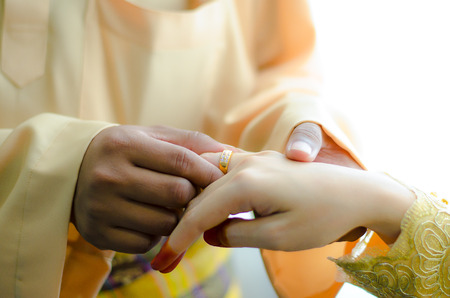 Malay wedding ceremony, Malaysia. Groom putting a diamond ring to his brides finger