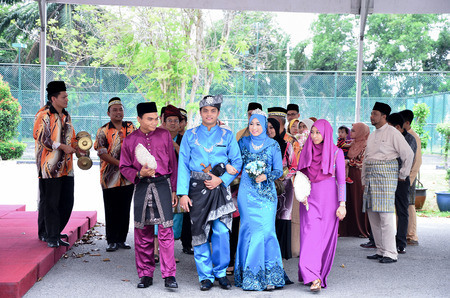 Kuala Lumpur, Malaysia  March 15, 2014. Malay Wedding Ceremony. A Malaysian couple newlywed holding hands and walking is being congratulated by their guests.