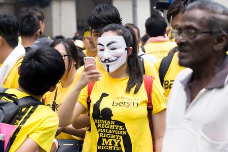 vendetta: Kuala Lumpur Malaysia - August 30, 2015. 2nd day of Bersih 4.0 Rally at Dataran Merdeka, Kuala Lumpur Malaysia. A lady with vendetta mask looking at her mobile phone. Editorial