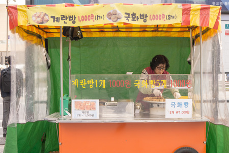 A lady grills and cook seafood dishes for customers at her stall in Seoul, South Korea. Street food is one of tourist attraction in Seoul.