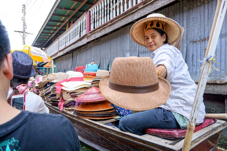 Bangkok, Thailand. Apr 5, 2015. The popular floating market in Ratchaburi. Damnoen Saduak Floating Market is one of Thailand largest. On seen, Thai lady selling straw hat on the boat. Editorial