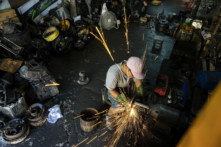 tolerate: Bangkok, Thailand . March 30, 2015. Man at work. A man doing his welding job without wearing face protection in workshop. Occupational safety in heavy industry is crucial and cant be tolerate.