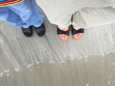 Selfie of couple feet at the beach. Top view of human feet standing on the sand at beach. Love and family concept. Stok Fotoğraf
