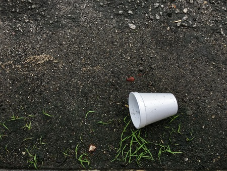 Environment and nature preservation concept. Empty plastic cup thrown away on the ground. Attitude, clean and hygiene concept.