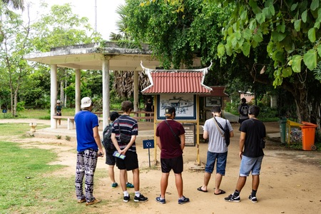 Tourist enjoying historical event and story at Cambodian Killing Fields where more than a million people were killed and buried by the Khmer Rouge regime. 
