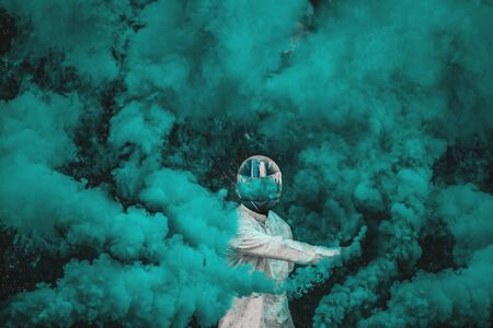 guy in mask standing in between blue smoke bombs
