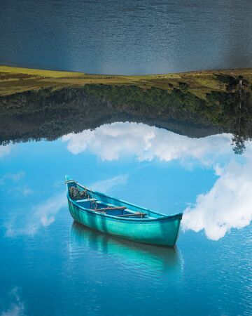 boat floating on reflection sky and lake upside down optical illusion