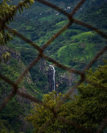 beautiful waterfall view throw fence, amazing landscape in Ooty India
