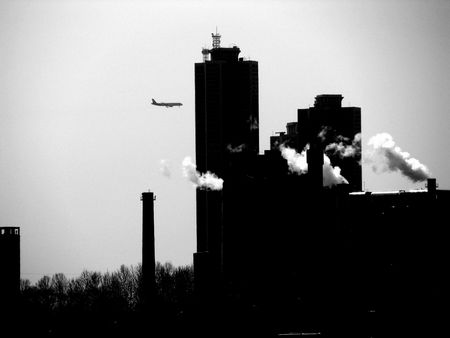 a factory in the middle of the city with a plane in the sky photo