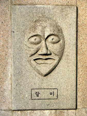 dissimulation: korean mask of a grandma carved in stone