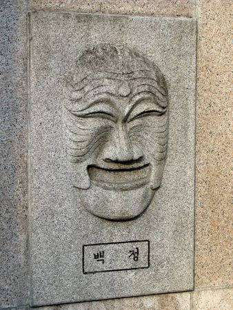 pretense: korean mask of a butcher carved in stone
