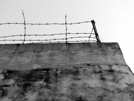 upraised: a high wall with iron fence on it Stock Photo