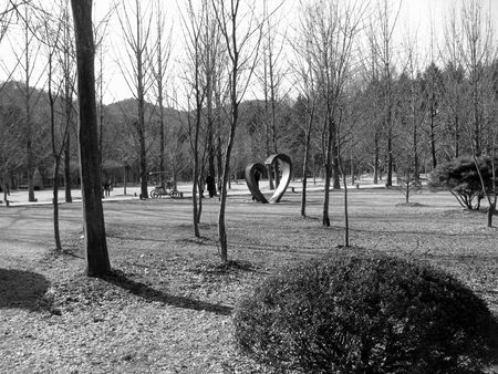 divergence: trees and heart-shaped statue in the park Stock Photo