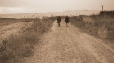 two pilgrims walking together on the road to santiago