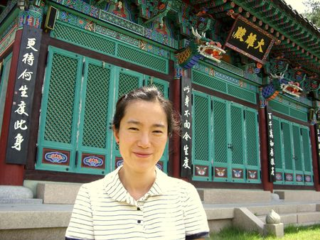 an asian woman in front of a buddhist temple photo