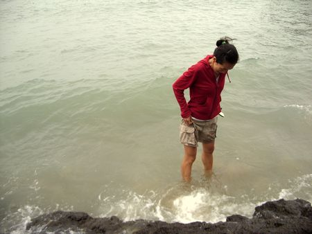 a girl with red jacket in the sea photo