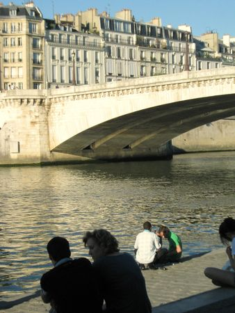 people sitting at the seine river in central paris photo