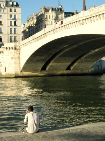 man sitting at the seine river in central paris
