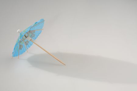 Tiny paper umbrella on white background, seasonal cocept, summer Stock Photo - 5063321