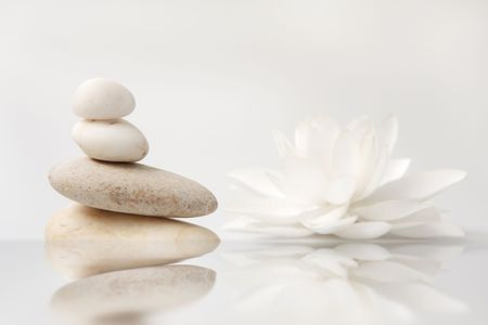 wellness still life pebbles and white lily, reflection in water, with waves,high key studio shot Stock Photo