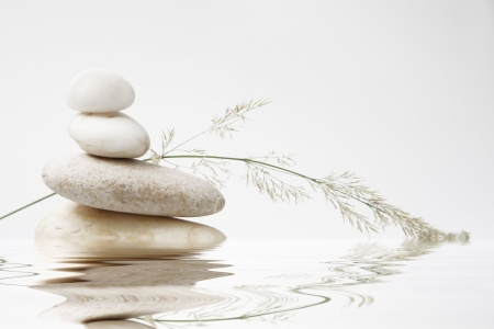 wellness still life, pebbles stacked with blade of wild grass,  reflection in water, high key studio shot,