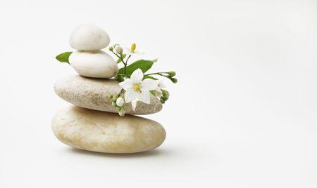 garden key: wellness still life: pebbles and white jasmine, high key studio shot
