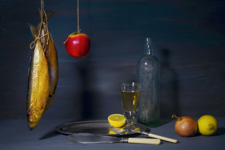 food still: vintage style food still life with smoked fish (kipper) wine and side dish Stock Photo