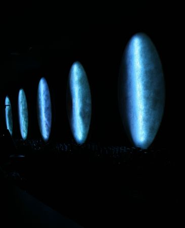 fiberglass: Dark abstract photo taken in a bar, showing unusual fiberglass light covers _just_ lighting a row of bottles Stock Photo