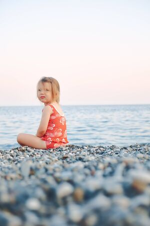 girl child sitting on a rocky shore on a background of the sea