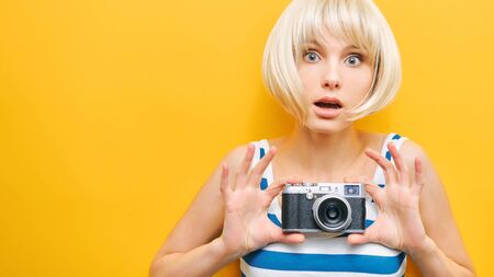 Portrait of a surprise girl with a camera in hand on a yellow background. Isolated studio 版權商用圖片