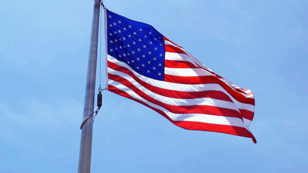 Flag of the United States of America waving on a sunny day against the blue sky, low angle view. The U.S, US, USA, American.