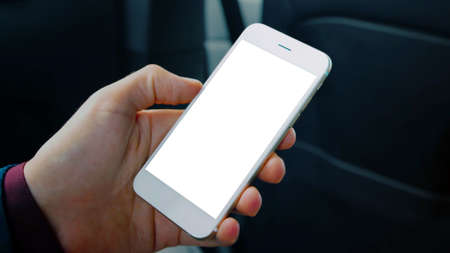 Man hand holding a cell phone with a blank white screen smartphone, interior car background, black copy space.