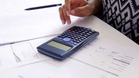 Women hand using a Scientific Calculator close up, exam preparation papers on the table. School or university study, maths and physics concept background.