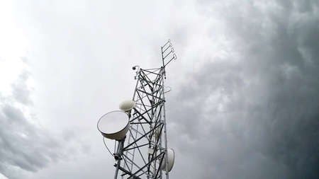 Radio antenna tower telecommunication against cloudy white sky in low angle view. Isolated background.