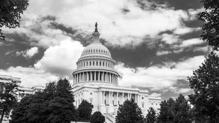 United States Capitol, the Capitol Building West front in low angle view against the cloudy blue sky. The United States of America Congress, Washington, D.C., USA, U.S. US. black and white.