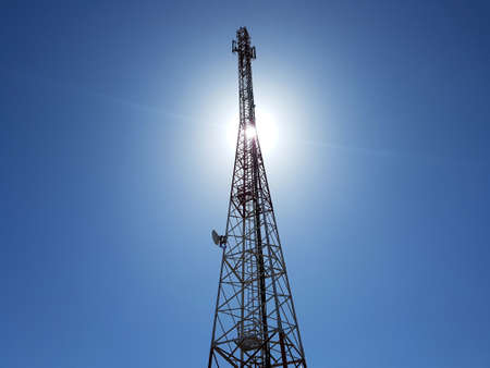 low angle view of cellular or mobile network tower against the sun in the blue sky. Foto de archivo