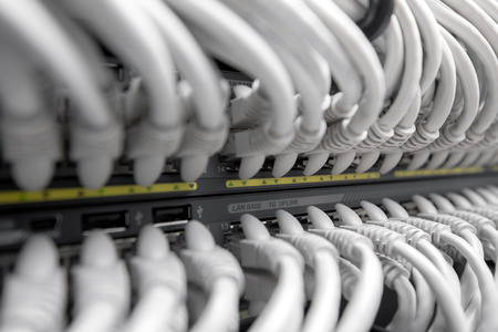 rj 45: Network Gigabit Smart Switch with network cables installed in the rack Stock Photo