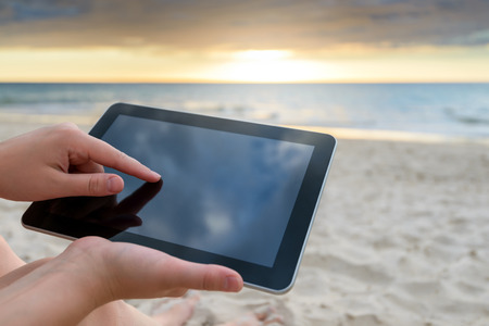 Woman holding a tablet at the beach during a warm sunset