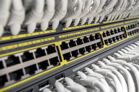 Network Gigabit Smart Switch with network cables installed in the rack 스톡 콘텐츠