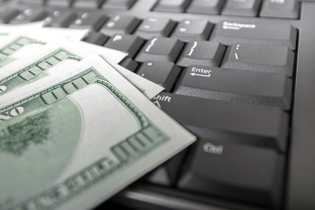 Money on computer keyboard Stock Photo