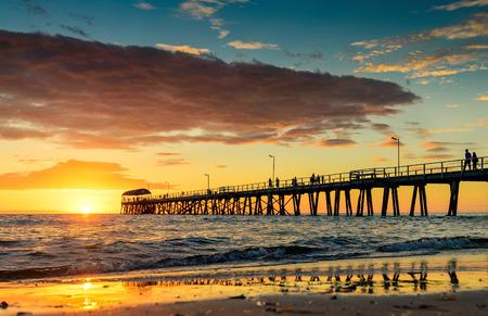 australia beach: People are walking on the Henley Beach Jetty at sunset
