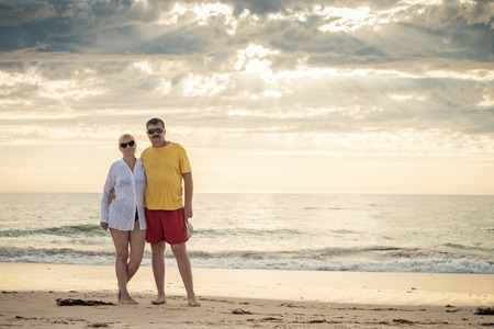 mid fifties: Happy mature couple in mid fifties at the beach. Warm color toning and natural light