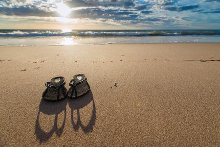 thongs: Thongs on the beach against a shoreline. Shallow DOF.